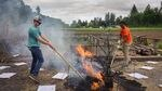 Two men use long-handled hand tools to tend to a fire burning outdoors.
