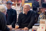 "Eric Alexandrakis (background), John Malkovich and Sandro Miller (right) sign copies of ""Like a Puppet Show"" for fans at Music Millennium"