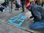 Toren McKnight of Central Point draws on the cement at the vigil for Aiden Ellison outside the Jackson County Justice Building