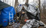 Jose Ortiz eats a boxed meal delivered by volunteers to the residence he built in the homeless encampment known as the Jungle on Monday, Dec. 7, 2020, in Ithaca, N.Y.