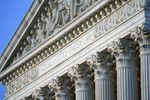 """A close up of the top of the Supreme Court building shows the words """"Equal justice under the law"""" carved into the marble of a classical style building."""