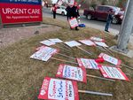 """Picket signs with messages like """"Support St. Charles Respiratory Therapy"""" lie on the grass outside St. Charles Bend Medical Center, near a hospital sign that reads """"Urgent Care."""""""