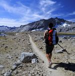 A hiker carrying a backpack looks towards a dusty trail, mountains and blue sky.