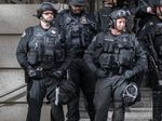 In this February 2020 photo supplied by a protest observer, Portland police Officer Corey Budworth, left, and Det. Erik Kammerer, right, are suited up in front of the Multnomah County Justice Center.