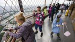 People look at a high-up view through a mesh fence.
