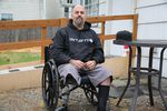 A person sits in a wheelchair and looks at the camera. He has only one leg.