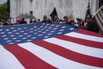 A group of Proud Boys unfurl a large American flag in front of the Oregon state Capitol during a rally to reopen Oregon in Salem on Saturday, May 2, 2020.