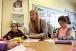 Teacher Michelle Moran, center, helps students with problems during small group work in a late-March class.