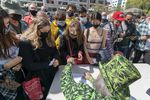 A person wearing a top had and suit jacket covered in images of cannabis plant leaves hands out joints to a crowd of people wearing  masks.