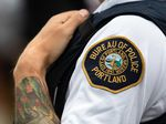 A liaison officer with the Portland Police Bureau watches people at a rally organized by the Proud Boys, labeled a hate group by the Southern Poverty Law Center, in Portland, Ore., Saturday, Aug. 17, 2019.