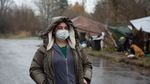 Jamie Spinelli stands bundled up in warm clothes and a mask, in front of a few tents at a homeless camp in Clark County. The weather is rainy.