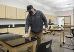 Areas that have been occupied by students at Reynolds High School in Troutdale, are cleaned and sprayed with disinfectant solution. Lead custodian, Ben Koskela wipes down a classroom worktable, March 26, 2021. Districts previously committed to distance learning have had to pivot under the governor's executive order to have schools open to in-person learning.