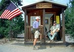 a wilderness ranger with a white beard and green hat sits on the porch of a small cabin and talks to a hiker wearing a purple shirt and fanny pack