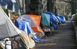 The tents of unhoused people who have set up encampments along a Portland sidewalk. At least seven tents are visible in the picture.
