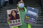 A pro-democracy activist holds placards with the picture of Chinese citizen journalist Zhang Zhan outside the Chinese central government's liaison office, in Hong Kong, Monday, Dec. 28, 2020. Zhang, a former lawyer and citizen journalist from Shanghai, has been sentenced to four years in prison for her reporting on the initial coronavirus outbreak in Wuhan, China. The activists demand the releases of Zhang, as well as the 12 Hong Kong activists detained at sea by Chinese authorities.
