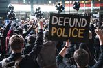 """A large crowd of protesters is seen from behind. One person holds a sign that says """"Defund police."""""""