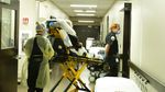 Medical crews move a patient on a hospital bed.