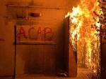 """A building is show on fire. The graffiti """"ACAB"""" is visible."""
