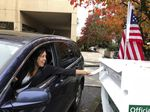 In this Nov. 6, 2018 file photo, a voter in Lake Oswego, Ore., places her ballot in a designated drop box outside City Hall. Two Oregon counties are offering the opportunity for U.S. military members, their dependents and others living overseas to vote in special elections this November with smartphones.