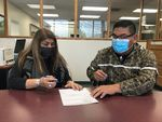 Nez Perce Tribal Executive Committee Chairman Shannon Wheeler (right) and Secretary Rachel Edwards sign paperwork completing the purchase of 148 acres of the tribe's ancestral land in Eastern Oregon.