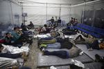 Young children lie inside a pod at the Donna Department of Homeland Security holding facility, the main detention center for unaccompanied children in the Rio Grande Valley run by U.S. Customs and Border Protection, in Donna, Texas, Tuesday, March 30, 2021. The children are housed by the hundreds in eight pods that are about 3,200 square feet in size. Many of the pods had more than 500 children in them. The Biden administration on Tuesday for the first time allowed journalists inside its main detention facility at the border for migrant children, revealing a severely overcrowded tent structure where more than 4,000 kids and families were crammed into pods and the youngest kept in a large play pen with mats on the floor for sleeping.