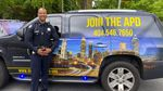 """A police officer stands in front of an SUV painted with the skyline of Atlanta, Georgia, and the text """"Join the APD 404.546.7650"""""""
