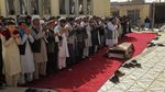 People pray during a funeral ceremony outside in Afghanistan.