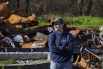 A person wearing a baseball cap and sweatshirt looks into the distance with the charred remains of a house in the background.