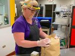 In the Baker School District, a food service employee prepares meals for students. All school staff will wear these face shields, created by Baker Technical Institute Students, for school programming this summer.