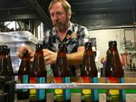 Double Mountain Brewery founder Matt Swihart grabs freshly bottled pale ale from the bottling line in Hood River. The brewery's new beer is among the first to be sold in Oregon's new refillable beer bottles.