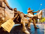 A piece from the Trump Statue Initiative depicts federal law enforcement officers pulling a Black Lives Matter protester into an unmarked van while the President takes a selfie.