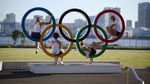 People sit on a statue of the Olympic rings