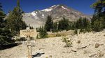 """a small brown sign that reads """"green lakes area"""" sits before a glaciated mountain peak against a deep blue sky"""