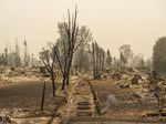 Smoke rises from the ground in a neighborhood destroyed by wildfire on Sunday in Talent, Ore. Hundreds of homes in Talent and nearby towns have been lost due to wildfire.