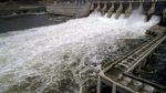 Water passes through the turbines of a dam, emerging in a frothy churn of whitewater.