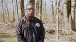 Darrell Wade stands with his held together in a wooded area. Portrait style.