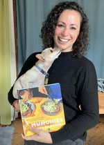"Farideh Sadeghin holds a very adorable dog and her cookbook, ""Munchies Guide to Dinner."""