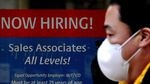 """A man in a mask stands in front of a sign that reads, """"Now hiring! Sales associates all levels!"""""""