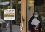 FILE - In this May 21, 2021 file photo, a sign reminds customers to wear their masks at a bakery in Lake Oswego, Ore. Oregon Gov. Kate Brown on Tuesday, Aug. 10, 2021 announced a statewide indoor mask requirement due to the spike in COVID-19 hospitalizations and cases, warning that the state's health care system could be overwhelmed.