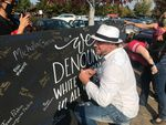 Nicholas Dieringer signs a board denouncing white supremacy in Bend on Oct. 3, 2020, after planning a pro-Trump rally in the same park as a picnic hosted by racial justice groups.