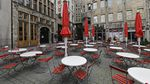 Dozens of tables and chairs are empty in a city square surrounded by old-fashioned European-style stone buildings.