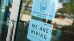 "In a shop window, one sign tells customers they must wear masks. Another sign says ""We are hiring."""
