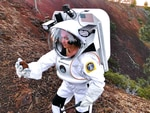 Spacesuit engineer Ashley Himmelmann in the Collins Aerospace spacesuit for analog studies examining and documenting a rock sample at Lava Butte via the spacesuit's integrated Information Technologies and Informatics Subsystem.