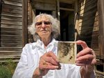 Ninety-year-old Ellen Simmons holds photo of herself standing on the porch of the Nelson House in 1929.