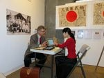 Obon Society co-founders Rex and Keiko Ziak working remotely during a temporary exhibit of yosegaki hinomaru flags in Portland in 2015.
