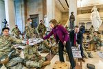 Rep. Vicky Hartzler, R-Mo., and Rep. Michael Waltz, R-Fla., hand pizzas to members of the National Guard gathered at the Capitol Visitor Center, Wednesday, Jan. 13, 2021, in Washington. as the House of Representatives continues with its fast-moving House vote to impeach President Donald Trump, a week after a mob of Trump supporters stormed the U.S. Capitol.