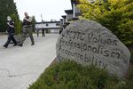 """Police officers walk down a sidewalk. A large boulder next to the sidewalk is incribed with the words """"WSCJTC values professsionalism accountability int --"""" the rest of the message on the rock is obscured by a bush."""