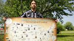 """A person holds a large map that shows the borders of the United States is labeled """"Native American Nations Our Own Names & Locations"""" and shows regions where different tribes live or have lived, instead of state and county boundaries."""
