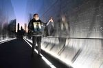 Claudia Castano (right) touches her brother German's name which is engraved at the Empty Sky 9/11 memorial at Liberty State Park in Jersey City, NJ on September 11, 2021.