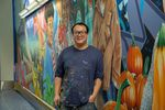 Alex Chiu stands in front of his mural in the north tunnel of the Portland International Airport
